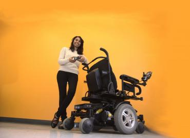 Pooja, founder of BrazeMobility is standing in front of wheelchair smiling.