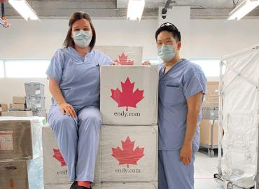 Two healthcare workers stand by the ENDY boxes donated.